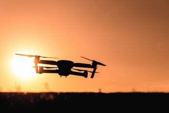 A drone flies across a sunset.