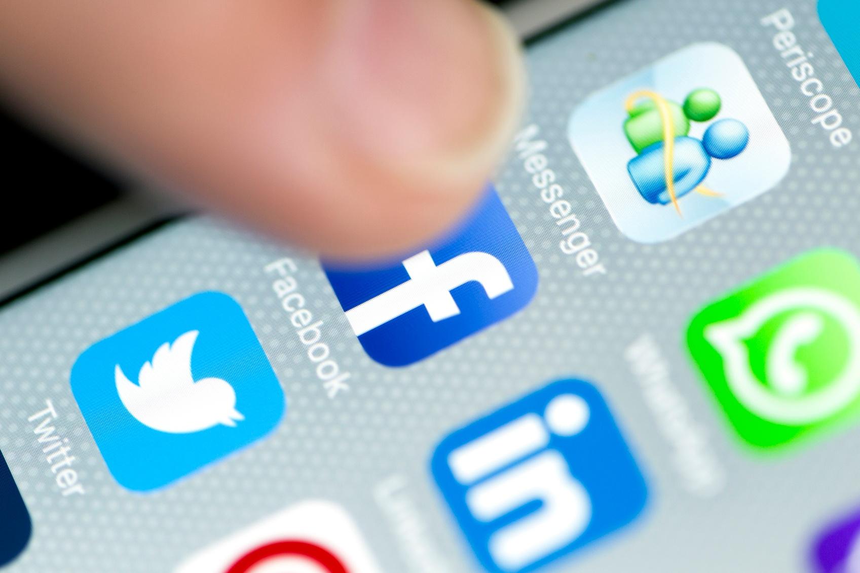 Male-Finger-is-Touching-Facebook-App-on-iPhone-6-Screen-000088471337_Medium.jpg