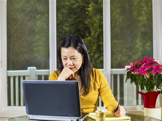 woman with serious expression looking at her laptop and writing
