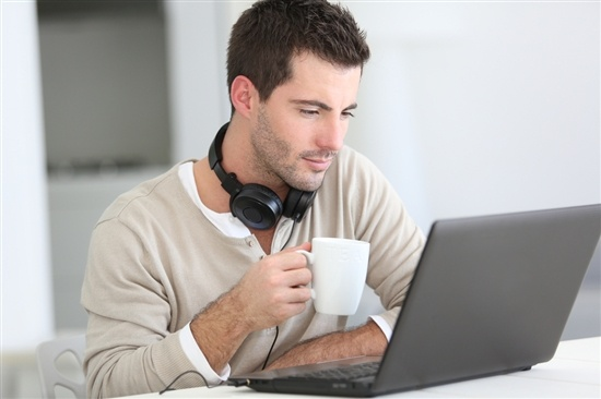 young man with headphones looking at laptop and drinking coffee
